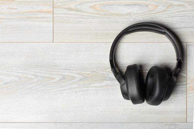 Bezprzewodowe słuchawki na białej drewnianej podłodze laminowanej tło dźwiękoszczelne muzyka i dźwięk w...