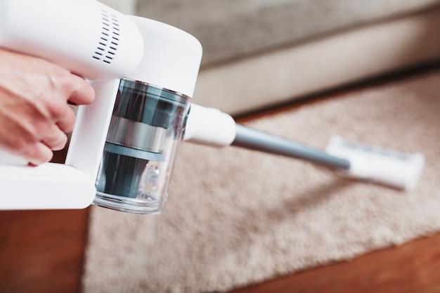 Bezprzewodowy odkurzacz od spodu nóżek czyści dywan w salonie. nowoczesne technologie sprzątania domu