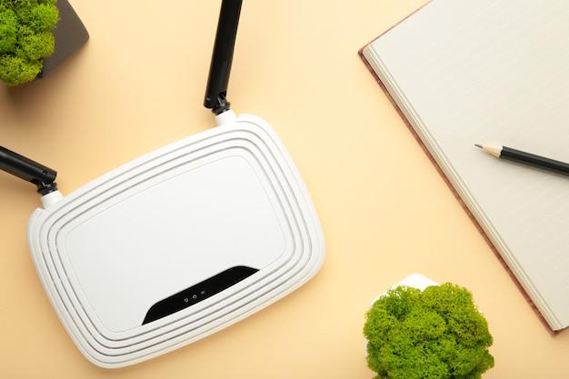 Bezprzewodowy router wi-fi na beżowej powierzchni z notebookiem na beżowym tle