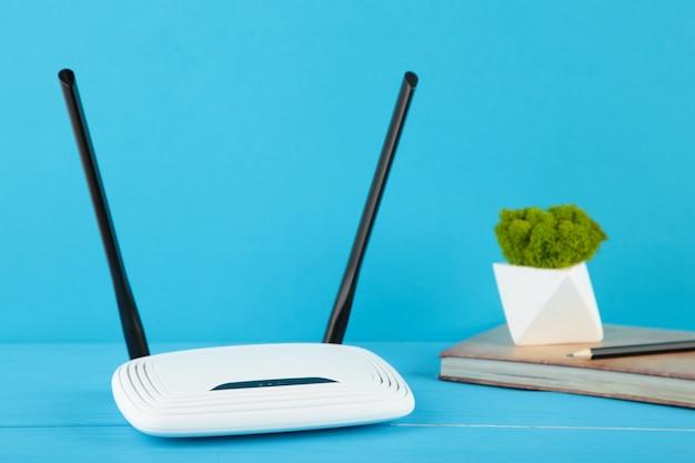 Bezprzewodowy router wi-fi na niebieskiej powierzchni z notebookiem w kolorze beżowym