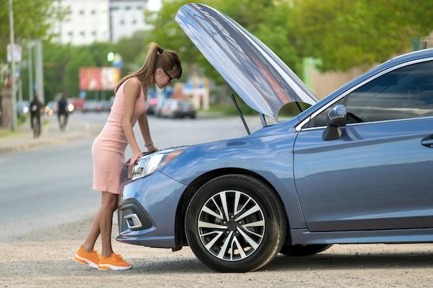 Bezradna kobieta stojąca obok swojego samochodu z otwartą maską, sprawdzająca uszkodzony silnik. młoda kobieta kierowca mający problemy z pojazdem.