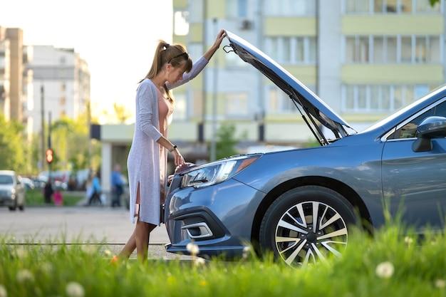 Bezradna kobieta stojąca w pobliżu swojego samochodu z otwartą maską, sprawdzająca uszkodzony silnik.