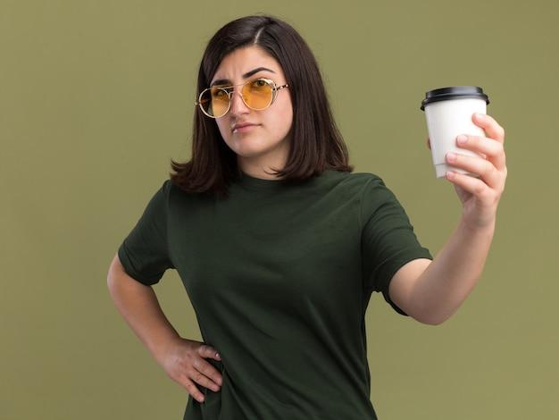 Bezradna młoda ładna kaukaska dziewczyna w okularach przeciwsłonecznych trzymająca papierowy kubek