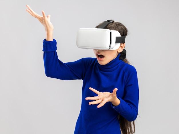 Bezradna nastolatka nosi zestaw słuchawkowy vr, patrząc na bok pokazując puste ręce na białej ścianie