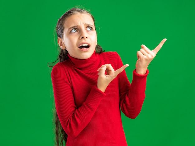 Bezradna nastolatka patrząca i wskazująca w górę odizolowana na zielonej ścianie