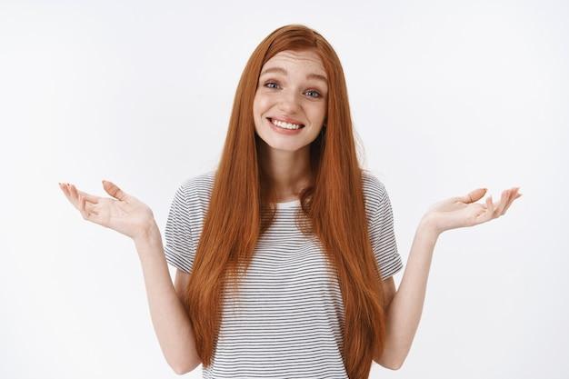 Bezradna urocza delikatna rudowłosa niebieskooka młoda dziewczyna uśmiechnięta nieświadomie wzruszająca ramionami rozłożonymi na boki nie mam pojęcia pytany przepraszam nie mogę odpowiedzieć, stoi wątpliwa biała ściana