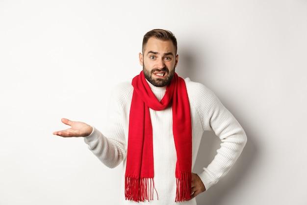 Bezradny brodaty mężczyzna nie wie, wzrusza ramionami i mówi przepraszam, stoi zakłopotany na białym tle