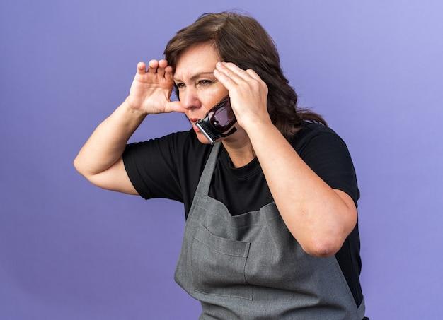 Bezradny dorosły kaukaski fryzjer żeński w mundurze trzymający dłoń na czole i trzymający maszynkę do strzyżenia włosów, patrząc na bok na białym tle na fioletowym tle z kopią przestrzeni