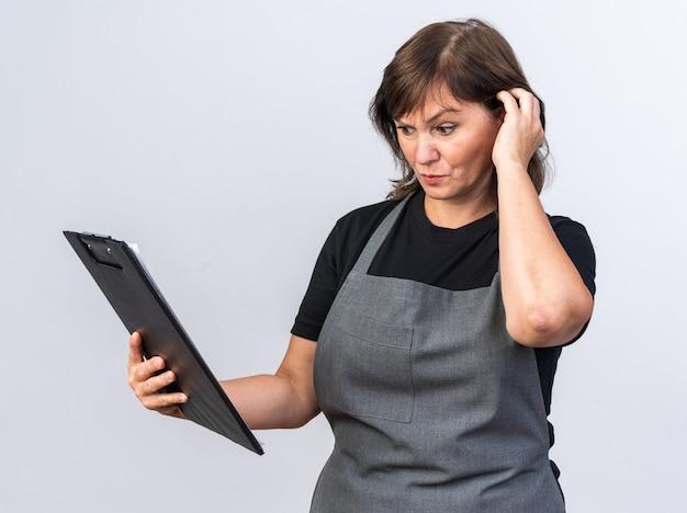 Bezradny dorosły kaukaski fryzjer żeński w mundurze trzymającym i patrzącym na schowek odizolowany na białej ścianie z miejscem na kopię