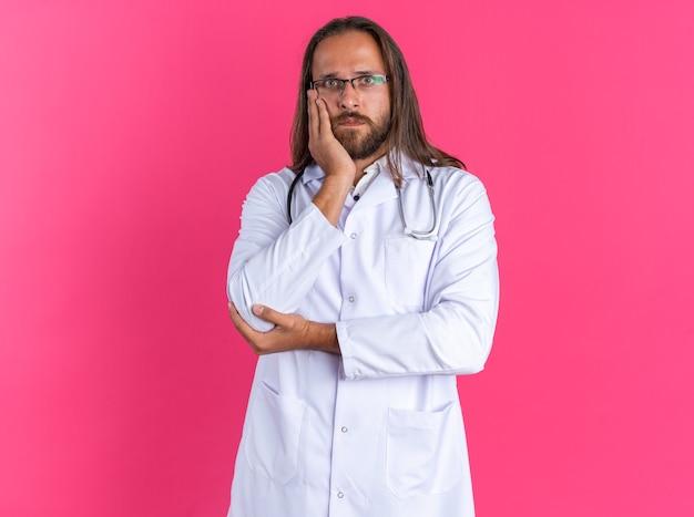 Bezradny dorosły mężczyzna lekarz ubrany w szatę medyczną i stetoskop w okularach trzymających rękę na twarzy i na łokciu, patrząc na kamerę odizolowaną na różowej ścianie z kopią przestrzeni