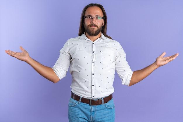 Bezradny dorosły przystojny mężczyzna w okularach, patrząc na kamerę pokazującą puste ręce izolowane na fioletowej ścianie