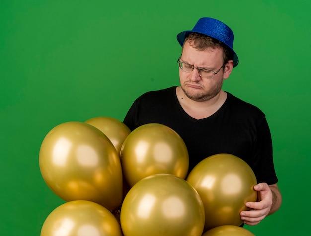 Bezradny dorosły słowiański mężczyzna w okularach optycznych w niebieskim kapeluszu imprezowym trzyma i patrzy na balony z helem