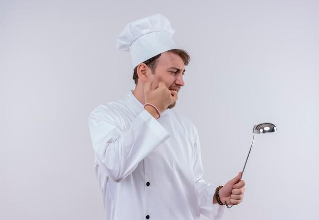 Bezradny młody brodaty szef kuchni w białym mundurze paląc rękę dotykając gorącej chochli na białej ścianie