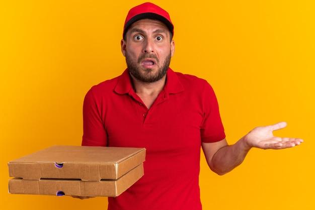 Bezradny młody kaukaski mężczyzna dostawy w czerwonym mundurze i czapce, trzymający paczki pizzy, patrzący na kamerę pokazującą pustą rękę odizolowaną na pomarańczowej ścianie