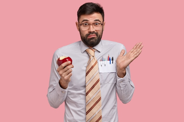 Bezradny, niezadowolony, brodaty mężczyzna rozkłada rękę, trzyma czerwone jabłko, nosi okulary optyczne i formalne ubranie, czuje wątpliwości
