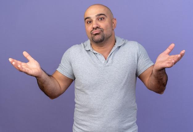 """Bezradny, przypadkowy mężczyzna w średnim wieku robi gest """"nie znam gestu izolowanego na fioletowej ścianie"""