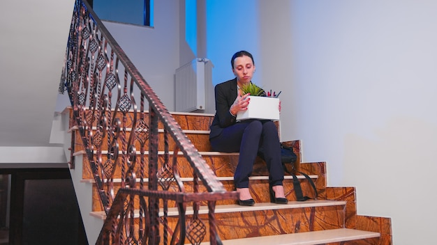 Bezrobotna bizneswoman trzyma pudełko rzeczy na schodach firmy po wyrzuceniu z pracy. koledzy opuszczają biurowiec. bezrobotna kobieta w depresji straciła miejsce pracy