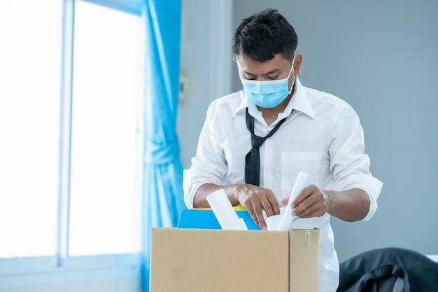 Bezrobotny biznesmen ma brązowe kartonowe pudełko i pisze list rezygnacyjny z powodu rezygnacji z pracy w związku z chorobą covid 19. koronawirus zmienił się w globalny kryzys.