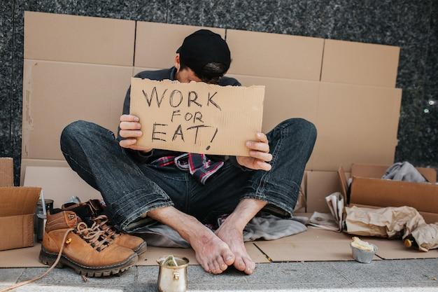 Bezrobotny facet siedzi na betonowym podłożu i zakrywa twarz znakiem pracy do jedzenia