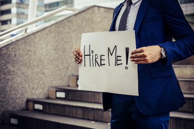 Bezrobotny mężczyzna rozpaczliwie szukający pracy. trzymając potrzebny znak pracy.