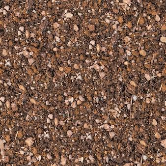Bezszwowa taflowa tekstura brązowej gleby z małymi kamieniami