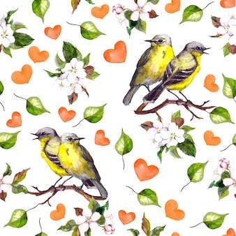 Bezszwowy wzór z dwa ptakami na kwiecistej gałąź, serca
