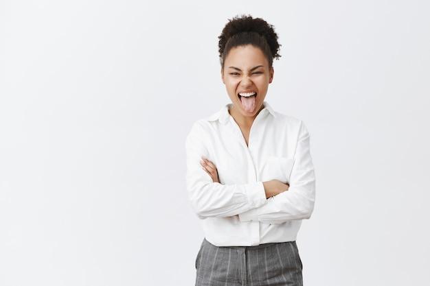 Beztroska afroamerykańska bizneswoman pokazuje język i dobrą zabawę