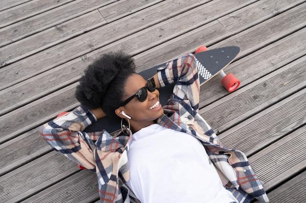 Beztroska afrykańska dziewczyna chłód leżąca na longboardzie słucha muzyki uśmiech i relaksuje miejski styl życia