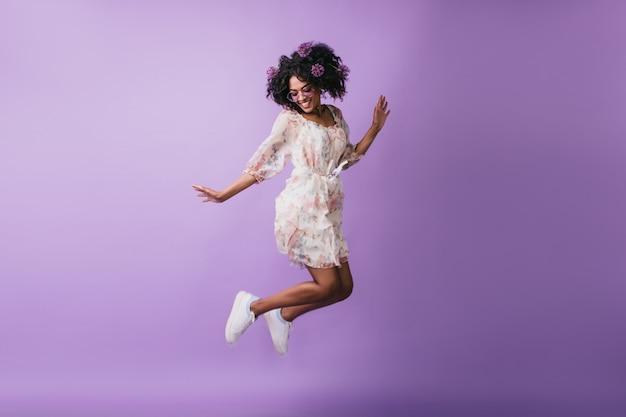Beztroska afrykańska dziewczyna w białych butach skoki. urocza modelka z kwiatami we włosach, taniec z radosnym uśmiechem.