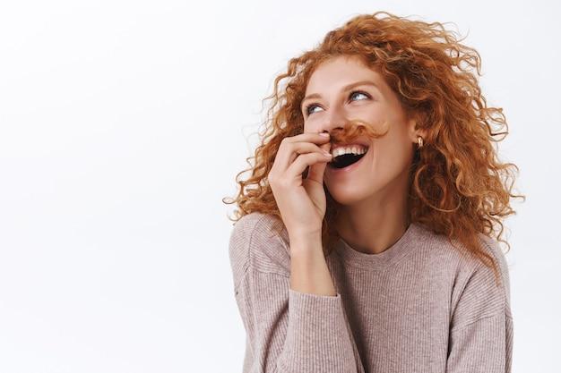 Beztroska, arogancka i pewna siebie elegancka, zabawna rudowłosa kobieta z kręconymi włosami trzymająca kosmyk i zakładana pod nos, aby zrobić wąsy, odwrócić głowę i uśmiechać się, śmiejąc się jak zły geniusz
