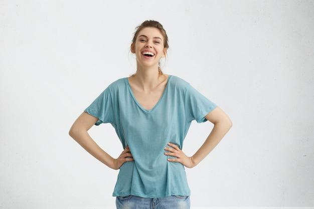 Beztroska atrakcyjna szczupła kobieta o ciemnych włosach, niebieskich oczach w luźnej niebieskiej koszulce i dżinsach, trzymając ręce na talii, uśmiechając się przyjemnie, pozując na białej betonowej ścianie