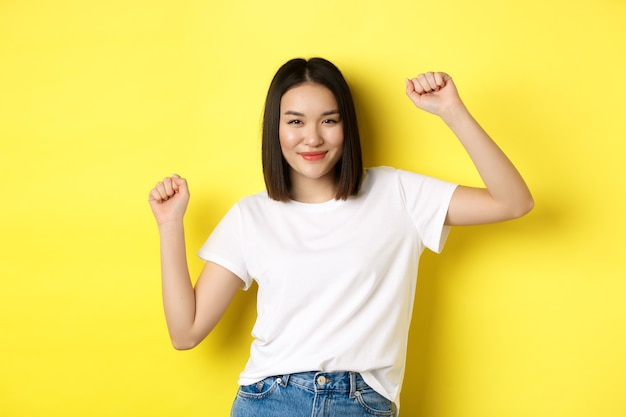 Beztroska azjatka tańczy i bawi się, pozuje w białej koszulce na żółtym tle.