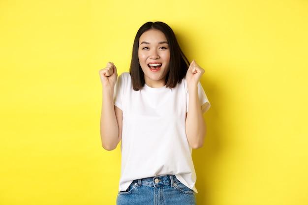Beztroska azjatycka dziewczyna tańczy i dobrze się bawi, pozuje w białej koszulce na żółtym tle.