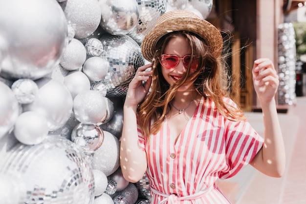 Beztroska biała dziewczyna w pasiastej sukience pozuje blisko błyszczących kulek. zewnątrz portret uroczej modelki w słomkowym kapeluszu chłodzenie w letni dzień.