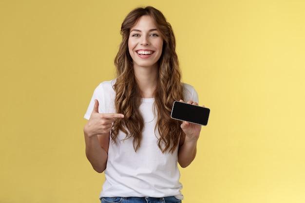 Beztroska, charyzmatyczna, urocza, kręcona kobieta-gracz lubi grać w gry na smartfonie pokazując własny wynik gry trzymaj telefon komórkowy w pozycji poziomej wskazując wyświetlacz śmiejąc się zadowolona rozbawiona. skopiuj miejsce
