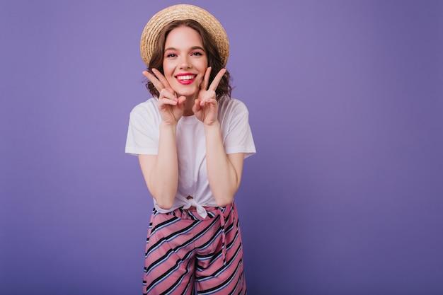 Beztroska ciemnowłosa dziewczyna pozuje z radosną miną na fioletowej ścianie. stylowa żartobliwa kobieta w słomkowym kapeluszu bawi się podczas sesji zdjęciowej.
