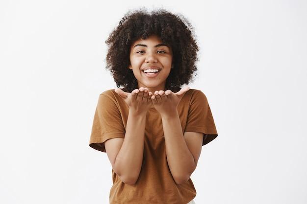 Beztroska, czuła i romantyczna afroamerykanka wyrażająca uczucie i miłość, wysyłająca pocałunek wiatru lub mwah, uśmiechnięta radośnie i trzymająca dłonie przy ustach nad szarą ścianą