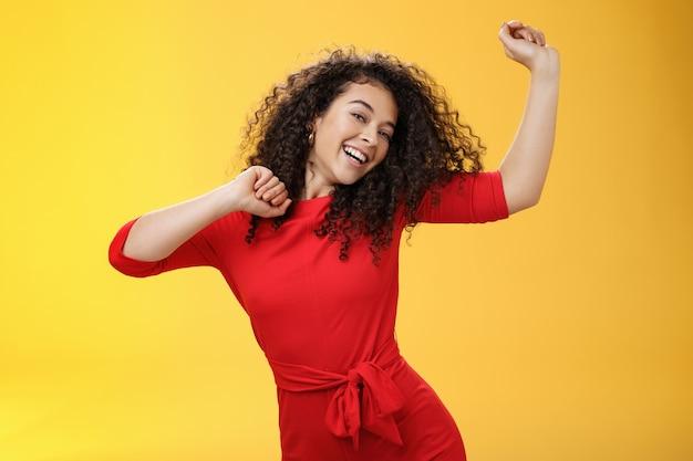 Beztroska dziewczyna czuje się podniesiona i radosna tańczy w czerwonej sukience, podnosząc ręce do góry szczęśliwie przechylając głowę i uśmiechając się szeroko do kamery, jak ciesząc się wakacjami, świętując święta na żółtym tle.