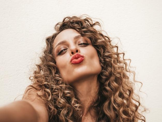 Beztroska dziewczyna pozuje wysyłając pocałunek na białej ścianie