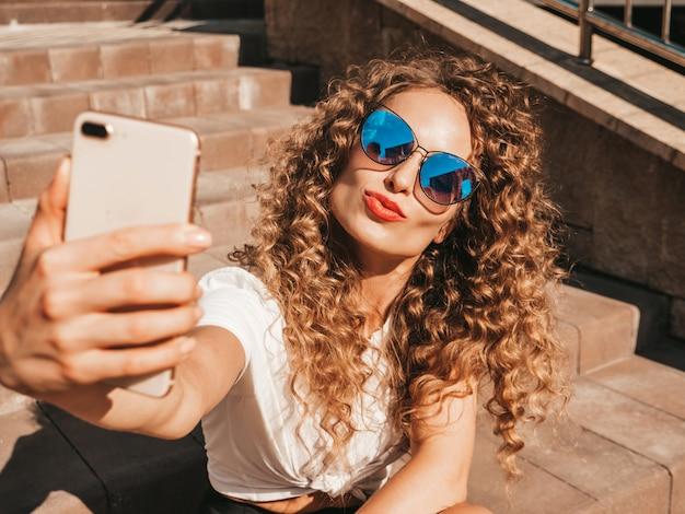 Beztroska dziewczyna siedzi na schodach na ulicy, biorąc selfie