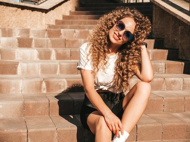 Beztroska dziewczyna siedzi na schodach na ulicy