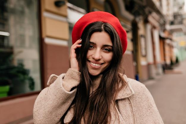 Beztroska dziewczyna w eleganckim kapeluszu pozowanie na kamery na tle starego miasta. zewnątrz portret błogiej długowłosej kobiety w beżowym płaszczu, śmiejąc się podczas spaceru po ulicy