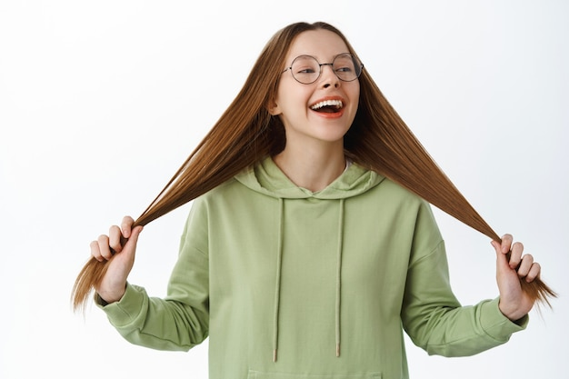 Beztroska dziewczyna w okularach, studentka bawiąca się długimi zdrowymi włosami, śmiejąca się i wyglądająca na szczęśliwą, stojąca w bluzie z kapturem na białej ścianie