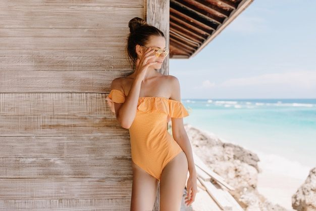 Beztroska dziewczyna w strojach kąpielowych vintage stojących w pobliżu drewnianego domu i patrząc na morze. odkryty zdjęcie pięknej brunetki kobiety z modną fryzurę relaksującą w ośrodku.