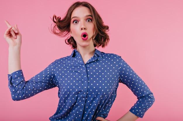 Beztroska europejska dziewczyna z małym tatuażem tańczącym na różowej ścianie. ekstatyczna ciemnooka dama w niebieskiej koszuli.