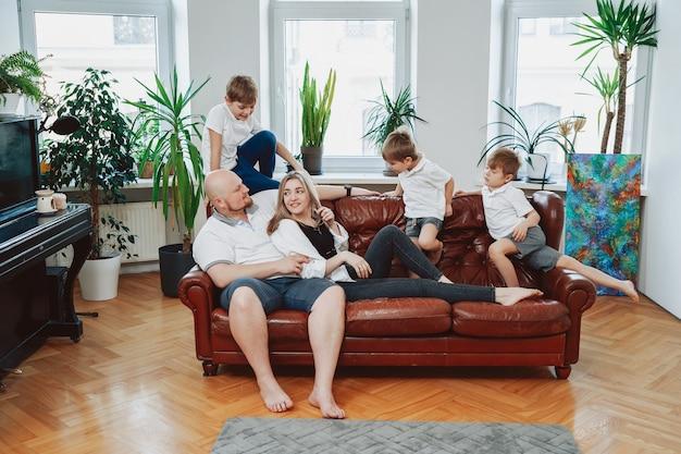 Beztroska i szczęśliwa rodzina dojrzałego mężczyzny i kobiety z małymi dziećmi siedzą na kanapie i bawią się.