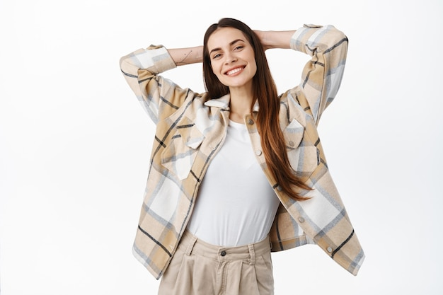 Beztroska i zrelaksowana młoda kobieta trzyma ręce za głową i uśmiecha się, odpoczywa w weekend wolny, nie ma nic do roboty, cieszy się leniwymi dniami, stoi szczęśliwa na białej ścianie