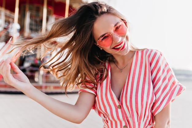 Beztroska kaukaska dama bawi się włosami w pobliżu karuzeli. podekscytowana piękna dziewczyna wyrażająca dobre emocje w parku rozrywki.