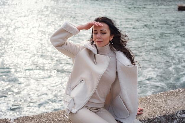 Beztroska kaukaska kobieta w beżowym ubraniu, ciesząca się widokiem na morze w ciepły, wietrzny dzień.