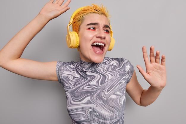 Beztroska kobieca hipsterka tańczy i śpiewa piosenkę, ma optymistyczny nastrój lubi słuchać muzyki w bezprzewodowych słuchawkach, nosi jasny makijaż izolowany na szarej ścianie